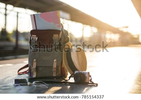 Map in Backpack ,Mobile phone with earphone and hat at the train station with a traveler.sun set, Travel concept. #785154337