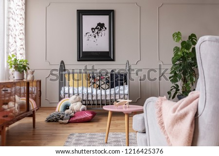 Map in black frame above grey crib full of colorful pillows and white bedding, real photo of baby room in vintage interior