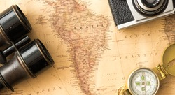 map of South America, Brazil among travelling accesories such as camera and compass