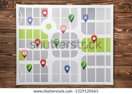 Map with location pointers on wooden background #1329120665