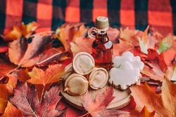 Maple syrup butter and taffy cones with leaf shape cookies on traditional Quebec plaid table with red autumn leaves. Small gift bottle. Traditional food.
