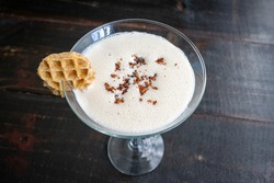 Maple Syrup Cocktail with Garnish: A sweet and creamy cocktail made with dark rum and maple syrup then topped with bacon bits and a mini waffle garnish