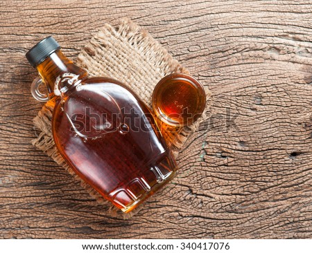 maple syrup in glass bottle on wooden table #340417076