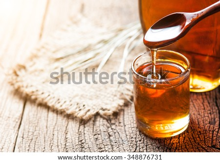 maple syrup in glass bottle on wooden table #348876731