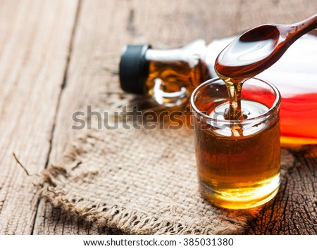 maple syrup in glass bottle on wooden table #385031380