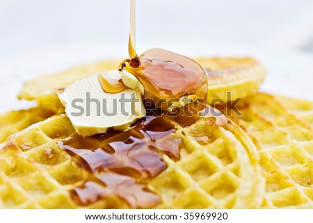 Maple syrup pouring onto waffles. Shallow DOF with focus on syrup and butter.