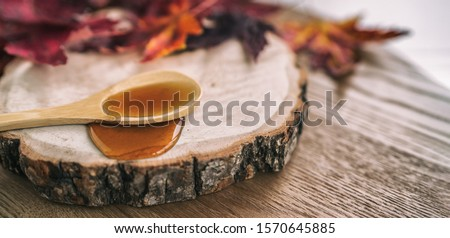 Photo of  Maple syrup sugar shack cabane a sucre restaurant from Quebec farm maple tree sap famous sweet liquid dripping from wooden spoon on wood log rustic sugar shack banner panoramic with red leaves.