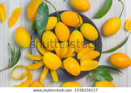 maprang yellow-orange fruit in black is placed in the middle and has a camparine around it on the cloth surface. Stok fotoğraf ©
