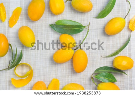 Maprang Yellow orange fruit With a sweet and sour taste mixed with appetizing, spread on the cloth floor Stok fotoğraf ©