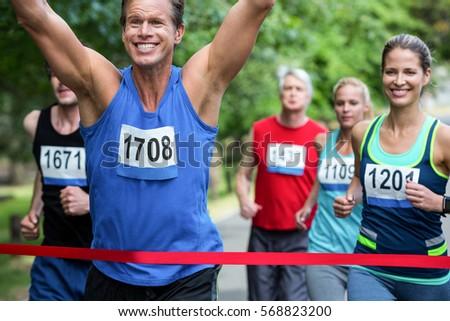Marathon male athlete crossing the finish line in park #568823200