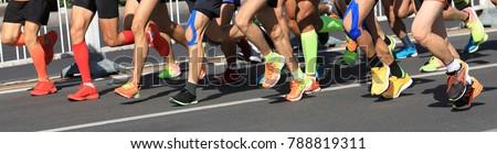 marathon runner legs running on city road #788819311