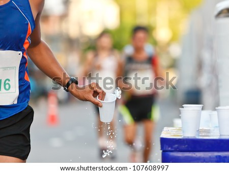 Marathon runner picking up water at service point