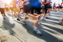 Marathon runners in motion. Running in the city, sun shining.