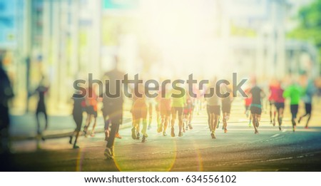 Photo of  marathon runners in the city background