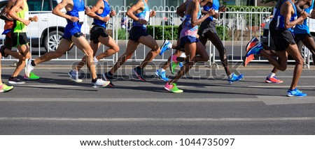 marathon runners legs running on city road #1044735097