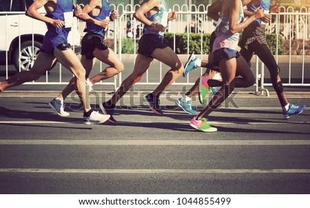 marathon runners legs running on city road #1044855499