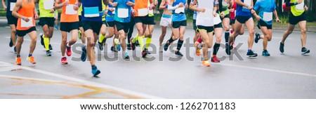 Marathon runners legs running on city road #1262701183