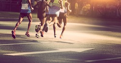 marathon runners running on city road