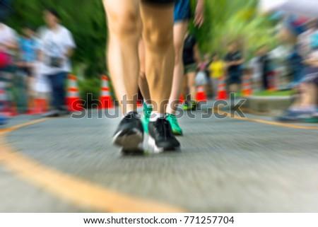 Marathon runners running on street, motion blur of legs. #771257704