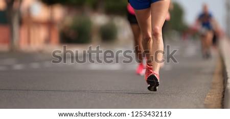 Marathon running in the light of evening, detail on legs #1253432119