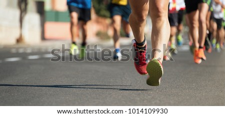 Marathon running in the light of evening,running on city road detail on legs.Copy space #1014109930