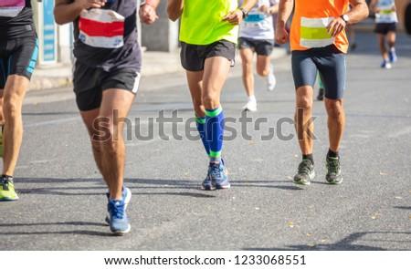 Marathon running race, group of runners on city roads, detail on legs #1233068551