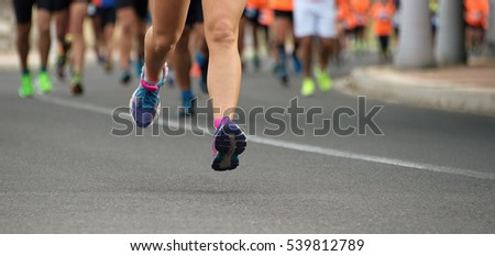 Marathon running race, people feet on city road #539812789