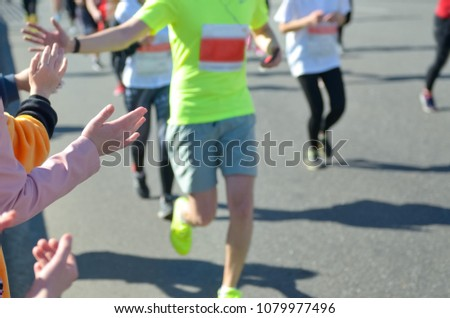 Marathon running race, support runners on road, child's hand giving highfive, sport concept #1079977496