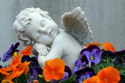 Marble angel statue in a cemetery among flowers