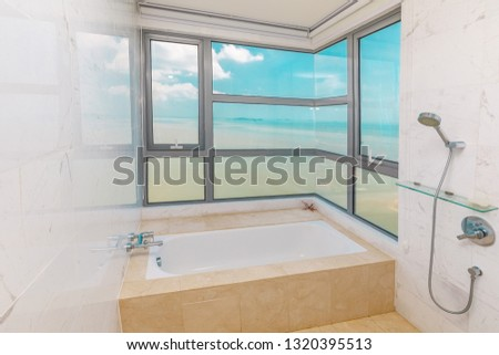 marble bathtub near window with astonishing seaview #1320395513