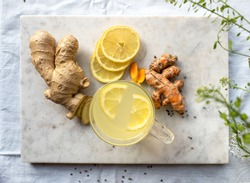 Marble board with immune system boosting ginger, lemon and turmeric hot tea on a set table.