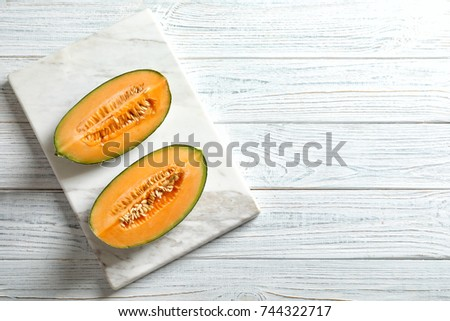 Marble board with slices of fresh ripe melon on wooden background