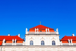 Marble decorative Sculptures on the rooftop . Tiled red roof of the castle