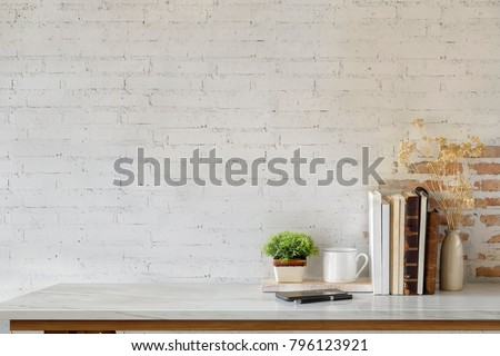 Marble desk with books, coffee mug, mobile phone and plant. Mock up