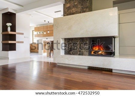 Marble fireplace in a vast living room with panelled floor, joined with bright kitchen #472532950