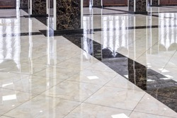 Marble floor in luxury lobby of office or hotel. Clean floor tile with reflections for background. Shiny stone floor in commercial building after professional cleaning service.
