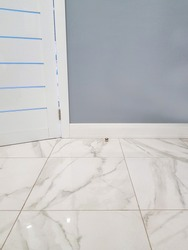 Marble floor. Square glossy tile with patterns, part of the wall and plastic baseboard