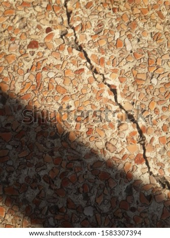 Marble floor with cracks and shadows on the floor. There are 3 colors: brown, light brown, dark brown.