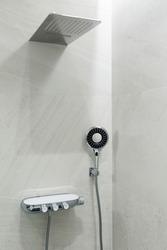 Marble gray wall, rain shower and shower head. Modern bathroom design. Vertically framed shot.