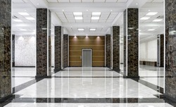 Marble interior of a luxury lobby of company or hotel. Clean corporate hallway with real floor tile. Shiny floor with reflections after professional cleaning. Service of modern office interior.