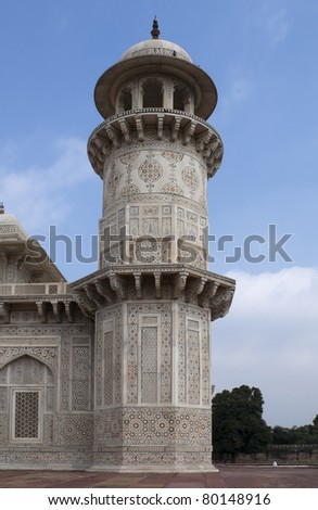 Marble minaret of Agra's Baby Taj mausoleum in India. White marble decorated tower against blue skies.