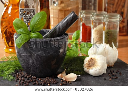 Marble mortar and pestle with fresh basil, dill, garlic, and peppercorns on slate cutting board.  Assorted spices and oils in soft focus in background.  Macro with shallow dof.