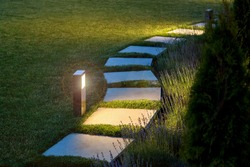 marble path of square tiles illuminated by a lamp glowing with a warm light in a night garden with a flower bed and a lawn, nobody.