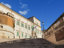 Marble stairs to Quirinal Palace or Palazzo del Quirinale, with flags, above entrance with balcony. Piazza del Quirinale, Rome, Italy.