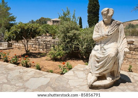 Marble statue in ancient site of Gortyn. Behind - basilica of Agios Titos. Crete, Greece