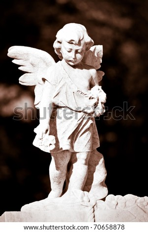 Marble statue of a child angel in sepia with a diffused background