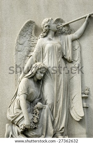 Marble statue of mourning woman kneeling beside angel with trumpet, copy space