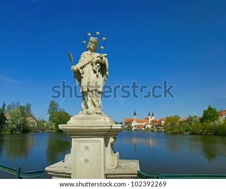 Marble statue of St.. John of Nepomuk and the panorama of the town Telc (Tel?). Czech Republic, World Heritage Site by UNESCO