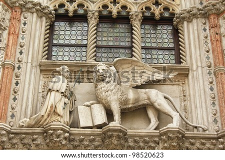 Marble statues of the winged lion (the symbol of Venice) and the doge Francesco Foscari above the Paper Gate (Porta della Carta) of the Doge Palace in Venice, Italy. Venetian Gothic architecture.