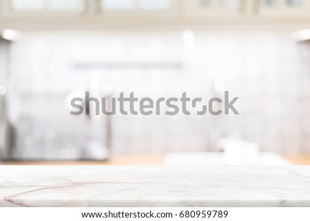 Marble stone countertop on blur kitchen interior background - can be used for display your products or food #680959789